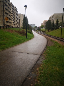 Multi-use paved trail running through a green space. Apartment and office buildings visible on either side of the green space