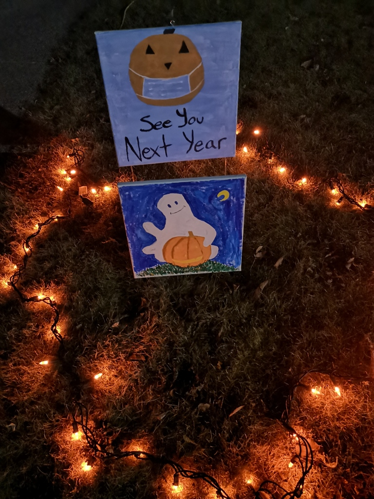 "Hand-painted sign with a pumpkin wearing a face mask and the message ""see you next year"" surrounded by orange lights."