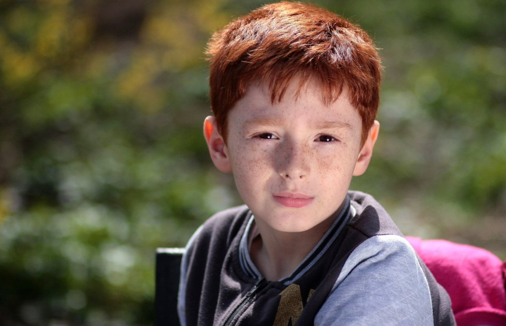 A white, red headed boy looking at the camera